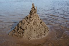 Sand castle on the beach against the water. Summer day stock images