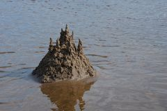Sand castle on the beach against the water. Summer day stock photography