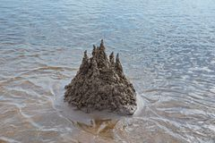Sand castle on the beach against the water. Summer day stock photo