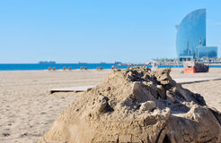 Sand castle beach with background buildings Stock Images