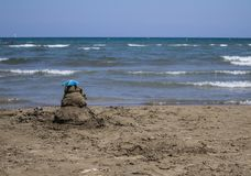Sand castle on the beach with blue sky and sea stock photos
