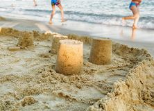 Sand castle on the beach. Child play in background stock image