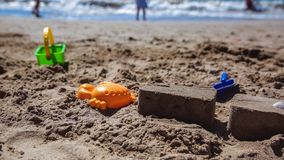 Sand castle on the beach with colorful toys and a small bucket stock photography