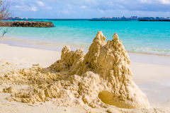 Sand castle on the beach in front of ocean with Male in the back. Sand castle on the sunny beach Royalty Free Stock Photo