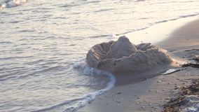 Sand castle on the beach. Ruined sand castle. Sea surfing on the resort coast stock video footage