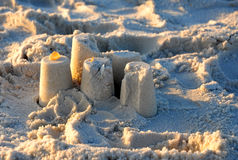 Sand castle on a Beach with the sunset casing shadows Royalty Free Stock Photo