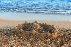 Sand castle beach wave stock images