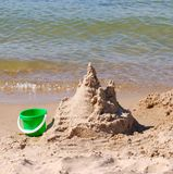 Sand castle and bucket. Abandoned sand castle and bucket at the side of a lake Stock Images