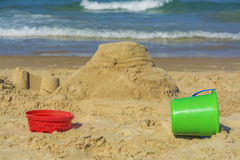 Sand castle and buckets on beach Stock Photos