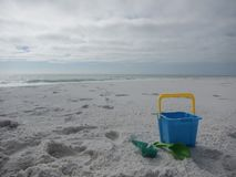 Sand castle building tools and bucket on a beach. White sand, ocean, and sky. Shell island Panama City Beach Florida. Gulf of Mexico royalty free stock photography