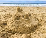 Sand castle building with towers on the beach with view on the sea royalty free stock photography