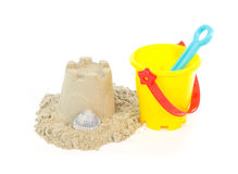 Sand castle built with a toy bucket. Sand castle built with a yellow toy bucket isolated on a white background stock photography