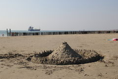 Sand castle with cargo ship in the background. A sandcastle on the beach, at the front. A large cargo ship in the background Stock Images