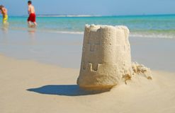 Sand Castle and Children. Sand castle and shadow on beach with playing children in background Royalty Free Stock Image