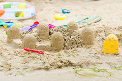 Sand castle circle and toys on the river bank Stock Photos