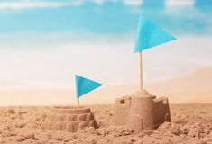 Sand Castle, Colosseum and blue flags on background of coast. royalty free stock photo