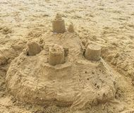 Sand castle construction with towers and shells on the beach sand landscape. Sand castle construction with towers and shells on the a beach sand landscape stock photo