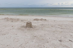 Sand castle on an empty beach on rainy day Royalty Free Stock Image