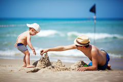 Sand castle. Father and son build sand castle Royalty Free Stock Photo