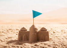 Sand castle with flag on the sea shore. stock photo