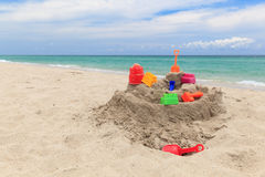 Sand castle and kids toys on beach Royalty Free Stock Photo