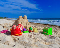 Sand castle with kids toys built on the beach Royalty Free Stock Image