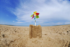 Sand castle with pinwheel on beach Stock Photo