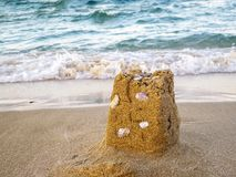 Sand castle remains with seashells, the sea in the background stock photos