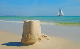 Sand Castle and Sailboat. Pristine sand castle on seashore with sailboat in distance Royalty Free Stock Image