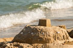 Sand castle on the seashore and a soft blue sea wave royalty free stock photography