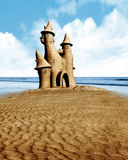 Sand castle and seaside. A very large sand castle built on a summer drenched beach with a bright blue sky and sea Royalty Free Stock Image