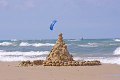 Sand castle and surfer in the sea Stock Photo