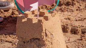Sand castle surrounded by beach toys royalty free stock image