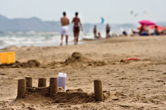 Sand castle and tourists on Spanish beach Royalty Free Stock Photo