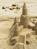 Sand castle tower and toy trucks royalty free stock image