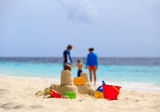 Sand castle and toys on tropical beach Royalty Free Stock Image