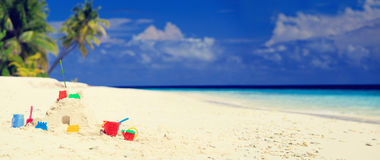 Sand castle on tropical beach and kids toys Royalty Free Stock Image