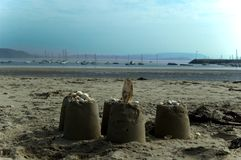 Sand castles on beach. Three sand castles on beach with harbor in background Stock Images
