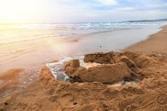 Sand castles on beach the sea. Waves wash away sand castles on beach the sea stock image