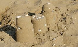 Sand castles on the beach with water shells royalty free stock image