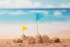 Sand castles and towers with flags on background of sea. Stock Photography