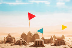 Sand castles, towers and flags Coliseum on background of sea. Royalty Free Stock Photography