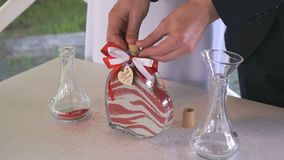 Groom closes tube of glass vessel filled with sand stock video