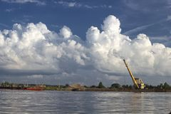 Sand charging on Volga, Russia with crane and boat. Sand charging on Volga, Russia. Boat, crane and beautiful cloudy sky royalty free stock photography
