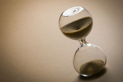 Sand clock. On beige background, time concept stock photography