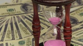 Sand clock. Close up. Sand clock, sand flowing through an hourglass, glass clock standing on the dollar bills, sand pink, time is sand, close up stock footage
