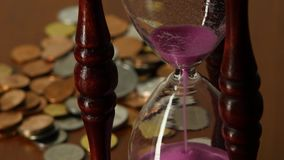 Sand clock. Close up. Sand clock, sand flowing through an hourglass, glass clock standing on the dollar bills, sand pink, time is sand, close up stock video footage