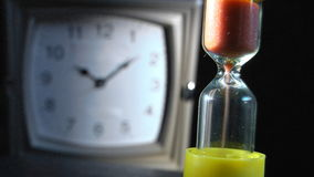 Sand clock. Close-up glass sand clock in front and unfocused clock in background stock video