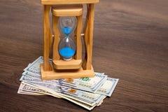 Sand Clock on dollar bills. Economy of time, time - money_ stock photos