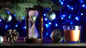 Sand clock that indicates the time remaining until Xmas, toys of winter holidays. Christmas background, a sand clock under a fir tree, indicating how long it is stock video